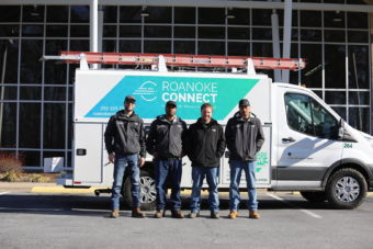 4 male employees standing in front of a Roanoke Connect service van