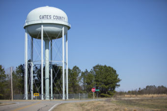Gates County water tower, road, trees