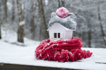 toy house wrapped in scarves and a hat outside