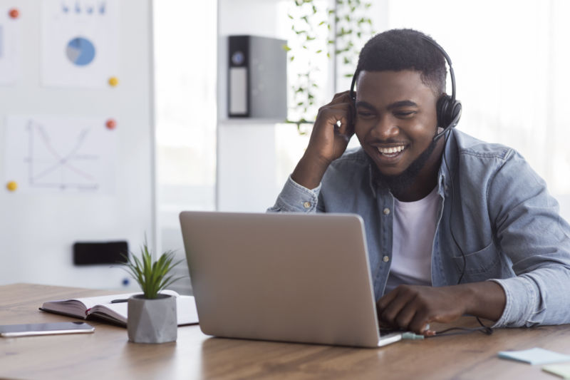 African American man smiling while wearing headphones and looking at laptop