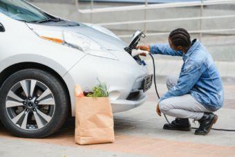 African American man recharging an electric car