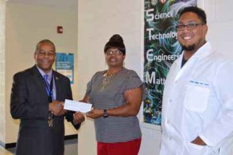 C.S. Brown High School STEM Principal Bobbie Jones (L) and teacher Eddie Hall accept an Operation RoundUp grant presented by Patrice Jordan of Roanoke Electric Cooperative