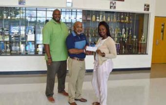 L to R: Bertie High School Principal Antonio Hoggard and Head Volleyball Coach James Woods accept a grant check from Ashley Horton of Roanoke Electric Cooperative