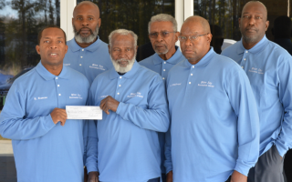 Group of African American men receiving a grant from Operation RoundUp