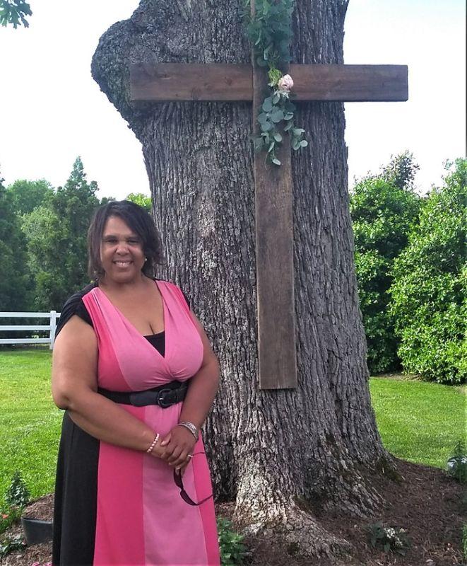 Avis Grey next to a tree