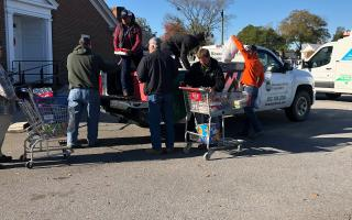 Volunteers at a canned food drive loading out of a pickup truck