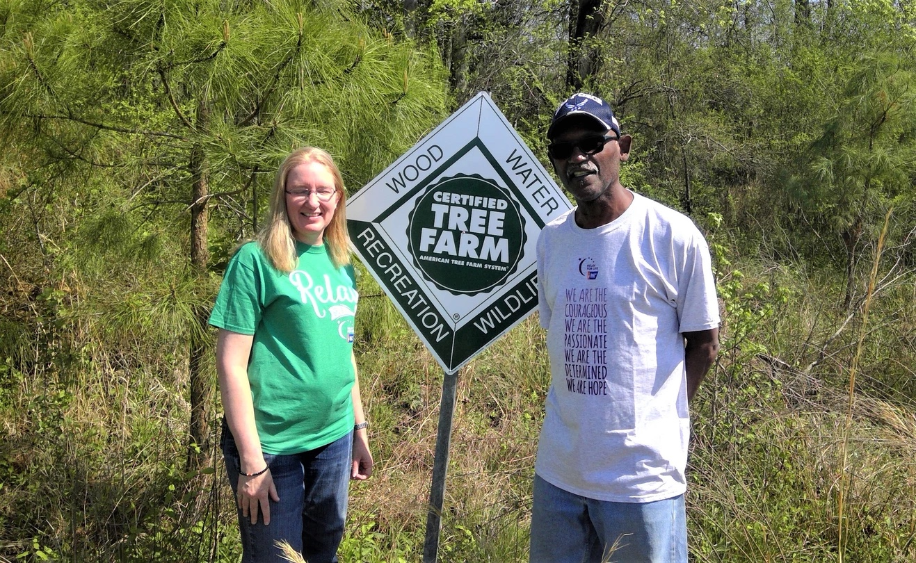 a man and a woman standing in front of a sign reading: Certified Tree Farm. American Tree Farm System. Wood,Water, Recreation, Wildlife.
