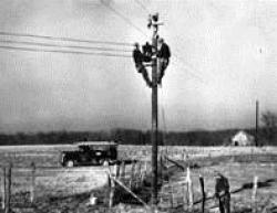 Black and white photo of linemen working on electrical pole