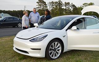 White electric car with 3 people standing next to it