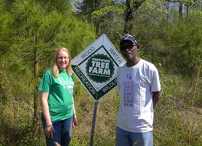Curtis and LaDonna Barnes with a sign for their tree farm