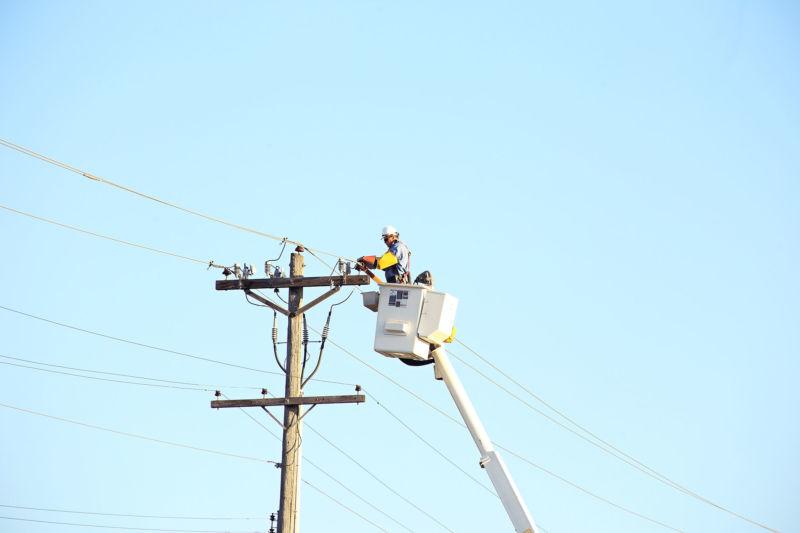 Lineman working on power poles