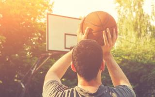 Young man shooting basketball at the hoop on a sunny day