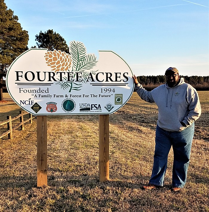 Tryrone Williams next to FourTee Acres sign