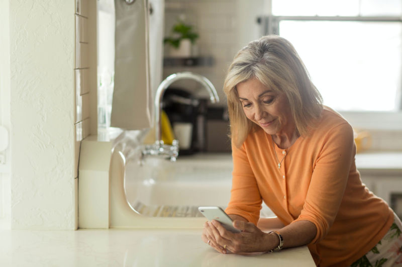Older woman using her phone while standing in kitchen